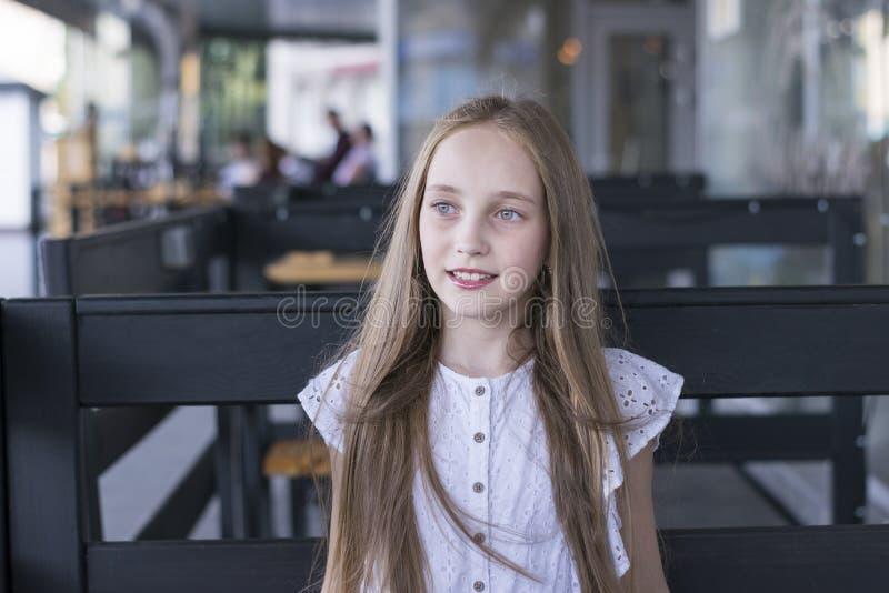 Śliczny blondynu model siedzi samotnie przy kawiarnią obraz royalty free