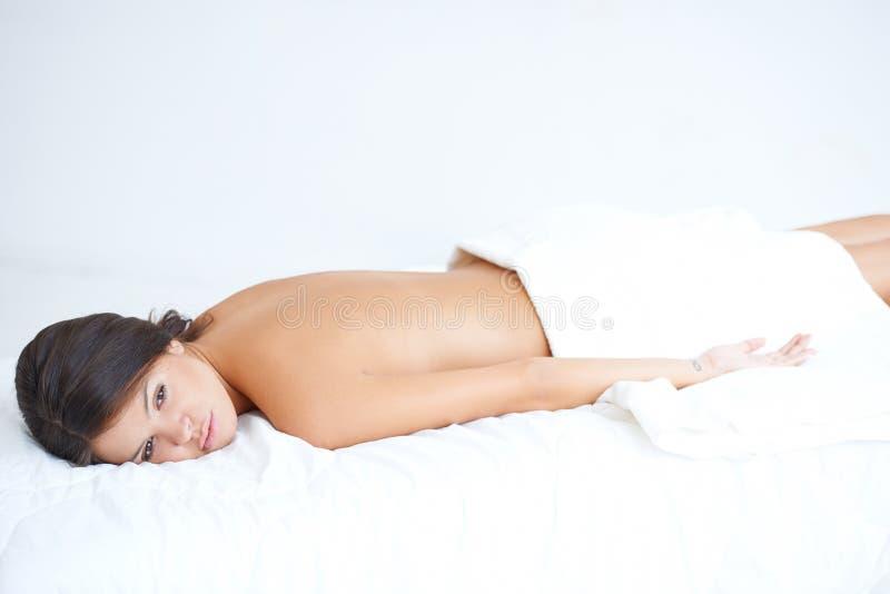 Śliczny brunetki lying on the beach na zdroju łóżku zdjęcia stock