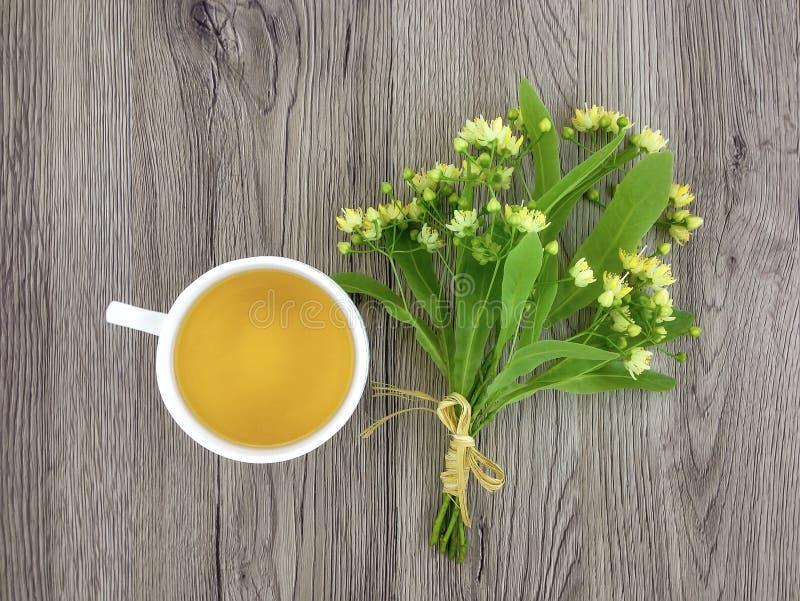 Śliczny bukiet lipowi kwiaty i herbaciana filiżanka na drewnianym stole Mieszkanie nieatutowy, odgórny widok zdjęcia stock