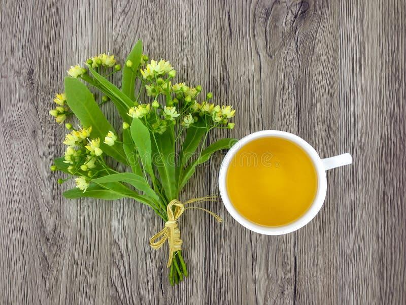 Śliczny bukiet lipowi kwiaty i herbaciana filiżanka na drewnianym stole Mieszkanie nieatutowy, odgórny widok fotografia stock
