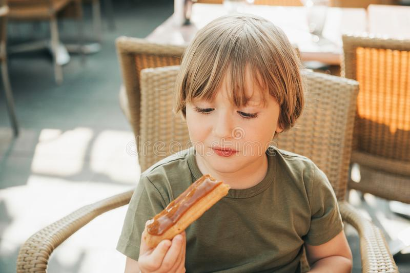 Śliczny chłopiec łasowania eclair tort obraz royalty free