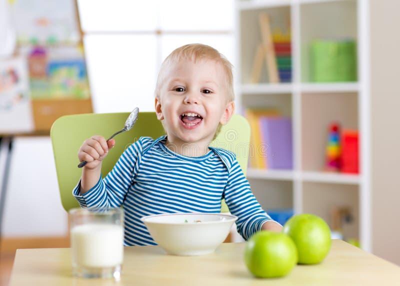 Śliczny chłopiec łasowania zboże z mlekiem w pepinierze zdjęcia royalty free