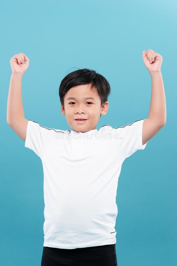 Śliczny chłopiec azjatycki uśmiecha się z podniesionymi ramionami zdjęcie royalty free