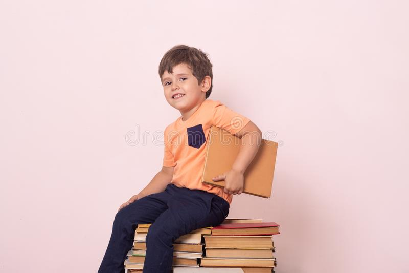 Śliczny chłopiec czytelniczej książki obsiadanie na stosie książki obraz stock