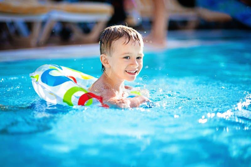 Śliczny chłopiec dopłynięcie w basenie w gumowym pierścionku, mieć zabawę w aquapark, szczęśliwi wakacje letni na plaży zdjęcia royalty free