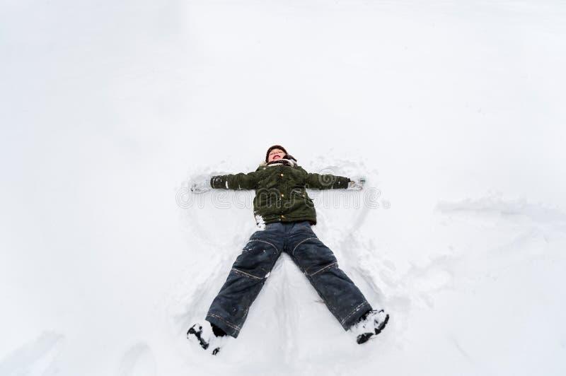 Śliczny chłopiec kłamstwo na białym śniegu Chłopiec ma zabawę na zima dniu obraz stock