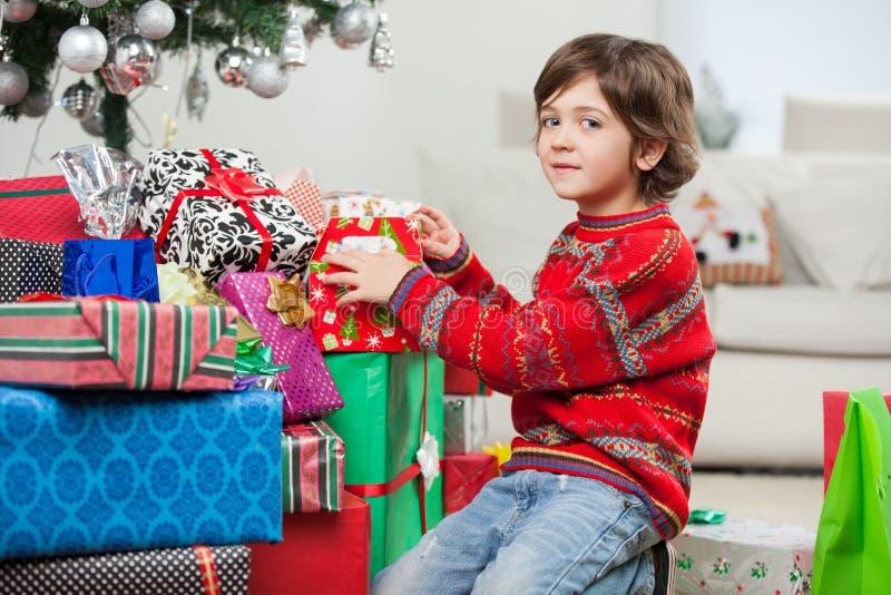Śliczny chłopiec klęczenie Bożenarodzeniowymi prezentami obrazy royalty free
