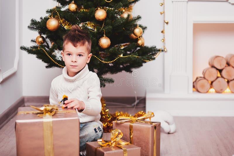 Śliczny chłopiec kucanie obok choinki obok mnóstwo prezentów z złocistymi faborkami i łękami, Facet w trykotowym sty i pulowerze fotografia stock