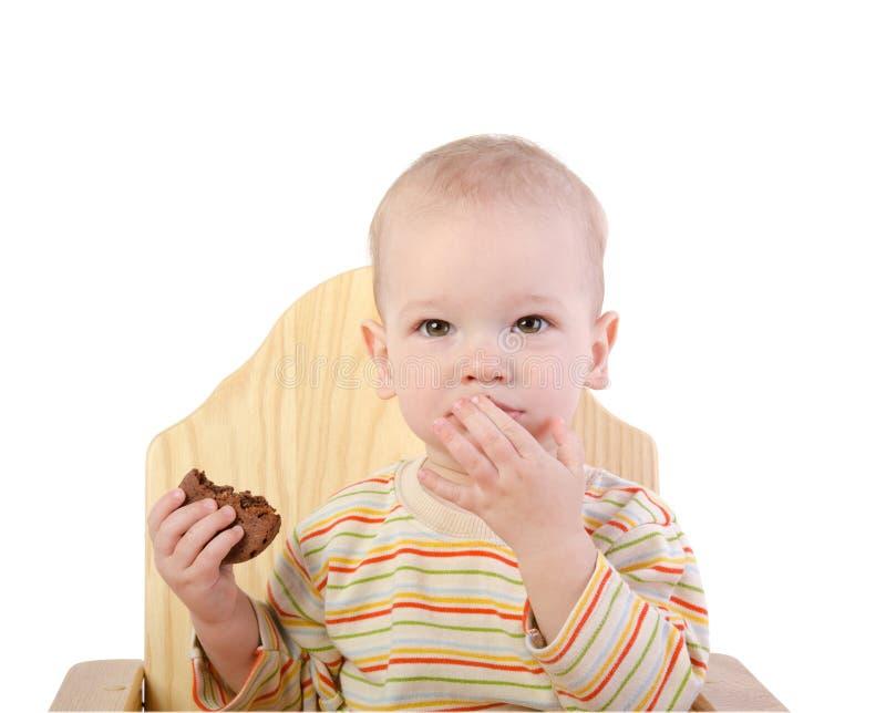 Śliczny chłopiec obsiadanie na łasowania ciastku i krześle obraz royalty free