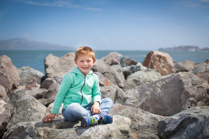 Śliczny chłopiec obsiadanie na dużych skałach obrazy stock