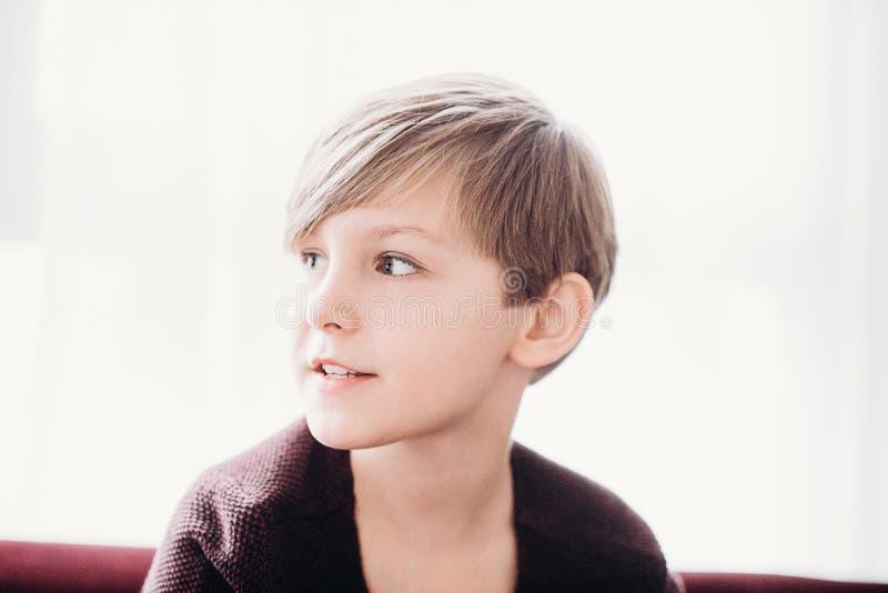 Śliczny chłopiec obsiadanie przeciw okno, miękka ostrość zdjęcie royalty free