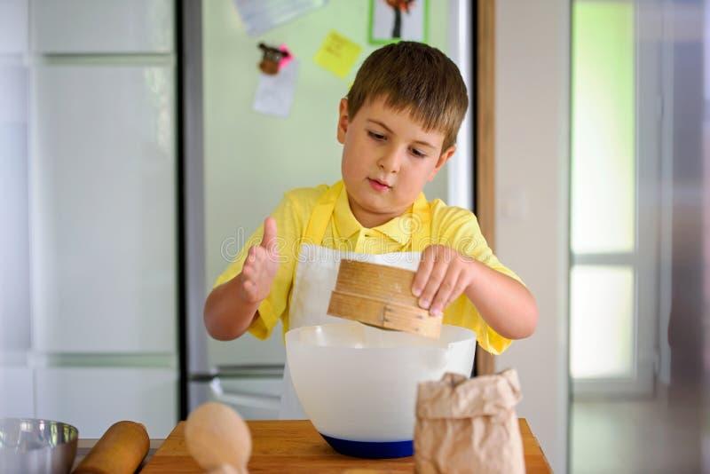 Śliczny chłopiec szef kuchni gotuje w domu obraz royalty free