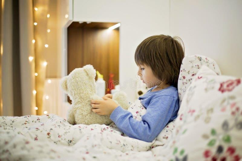 Śliczny chory dziecko, chłopiec, zostający w łóżku, bawić się z misiem obraz stock