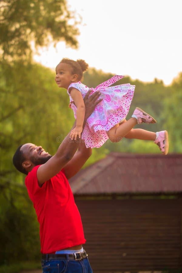Śliczny czarny ojciec i dziewczynka bawić się wpólnie obraz stock