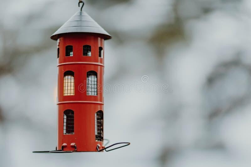 Śliczny, czerwony kruszcowy birdhouse w zima krajobrazie, obraz stock