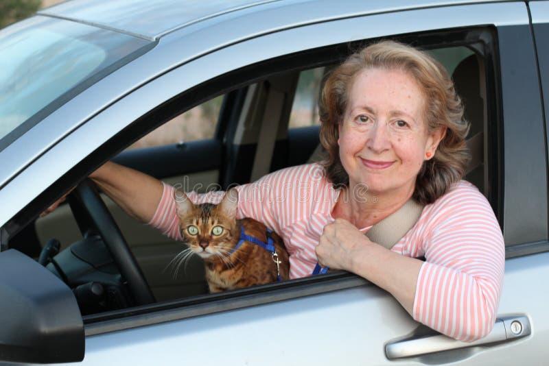 Śliczny dojrzały żeński kierowca z jej kotem fotografia stock