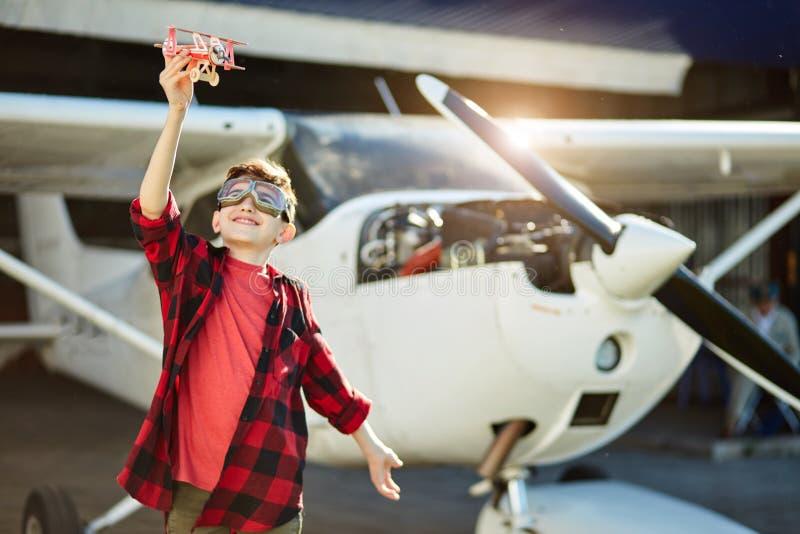 Śliczny dzieciak bawić się z małym zabawkarskim samolotem który zrobił jego ojca zdjęcia stock