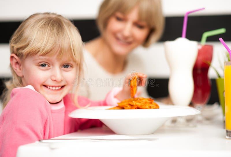 Śliczny dzieciak cieszy się makaron i sok obraz royalty free