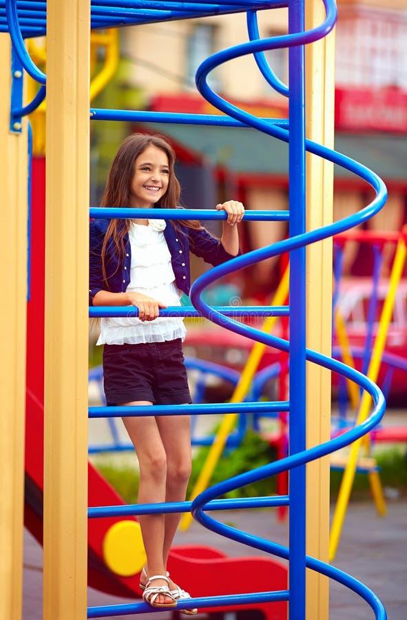 Śliczny dzieciak, dziewczyna wspina się na przełazie przy boiskiem zdjęcie stock