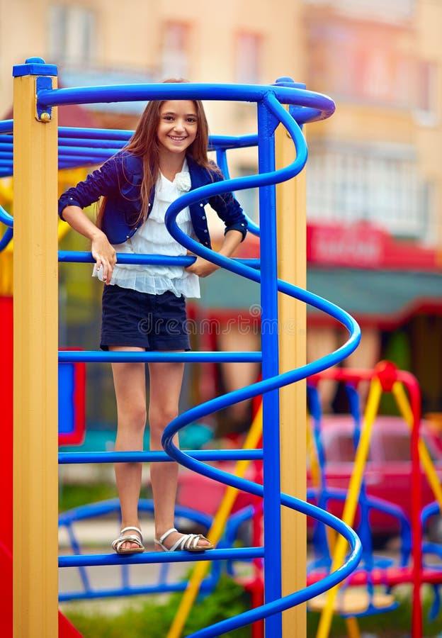 Śliczny dzieciak, dziewczyna wspina się na przełazie przy boiskiem zdjęcia stock
