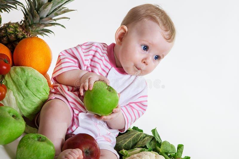 Śliczny dziecka obsiadanie z owoc i warzywo obraz stock