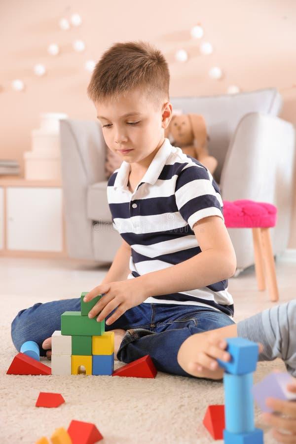 Śliczny dziecko bawić się z elementami na podłoga, indoors fotografia royalty free
