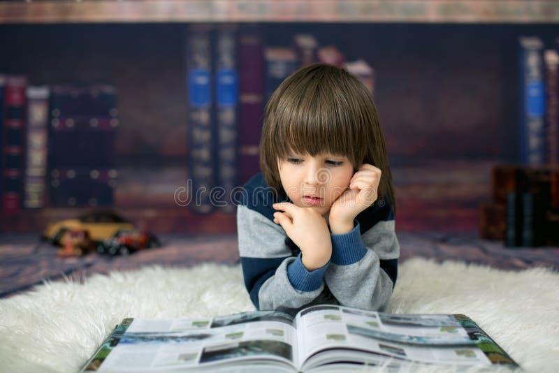Śliczny dziecko, chłopiec, czyta książkę przed biblioteką w domu obraz royalty free