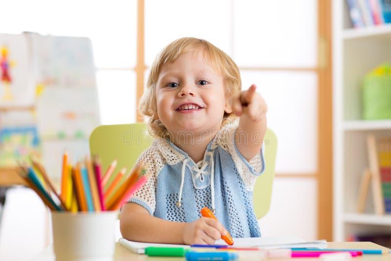 Śliczny dziecko chłopiec rysunek z porady piórem w dzieciniec sala lekcyjnej zdjęcie royalty free