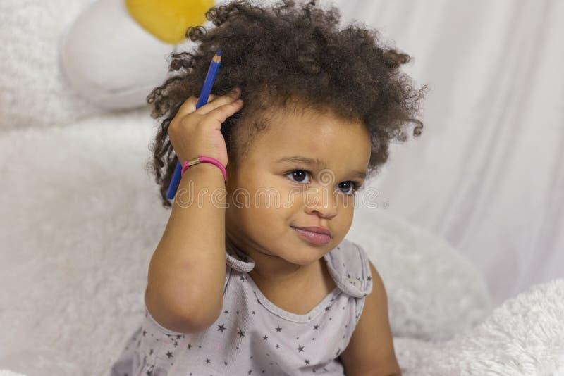 Śliczny dziecko dotyka kędzierzawego włosy obrazy royalty free
