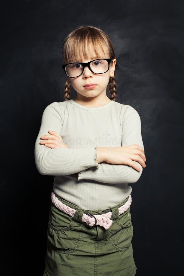 Śliczny dziecko myśleć przeciw szkolnemu sali lekcyjnej blackboard tłu w szkłach obraz stock