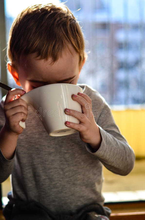 Śliczny dziecko pije herbaty zdjęcia royalty free