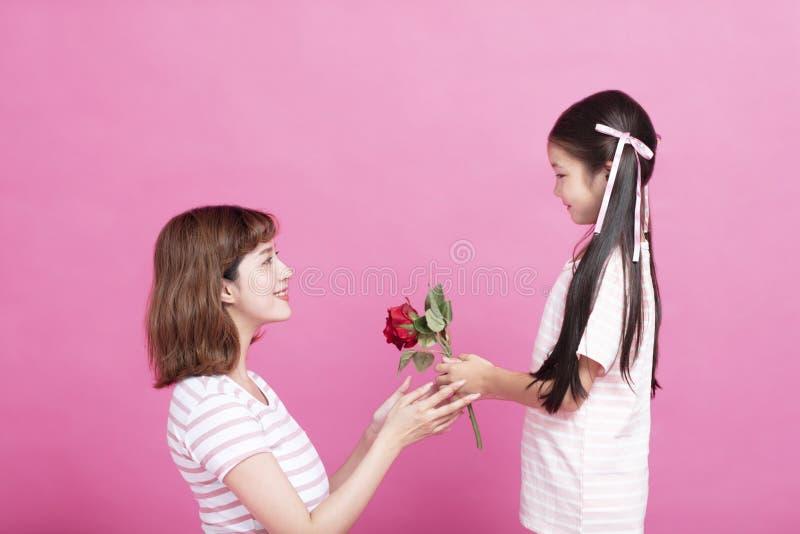 Śliczny dziecko przedstawia czerwieni róży matkować fotografia royalty free