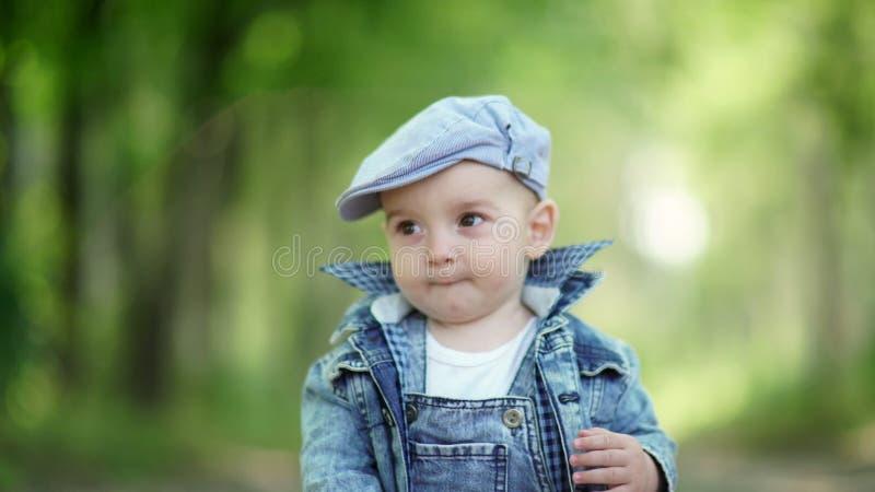 Śliczny dziecko trochę jabłczana chłopiec Berbeć w drelichowym kostiumu i nakrętce fotografia stock