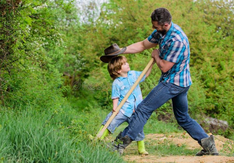 ?liczny dziecko w naturze ma zabawa kowboja taty Znalezisko skarby Ch?opiec i ojciec z ?opat? szuka skarby obraz stock