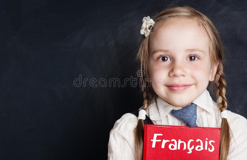Śliczny dziecko z książką w Francuskiej językowej szkole zdjęcia royalty free