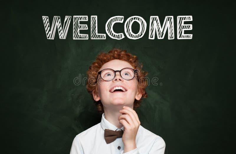 Śliczny dziecko z welkome tekstem na blackboard tle zdjęcia royalty free