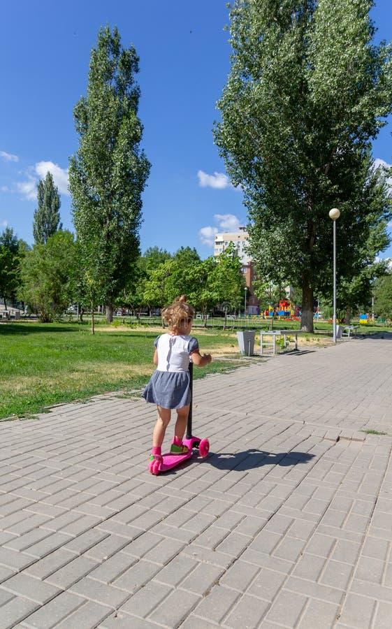 Śliczny dziecko zręcznie jeździć na łyżwach na różowej dwukołowej hulajnoga na s zdjęcia stock