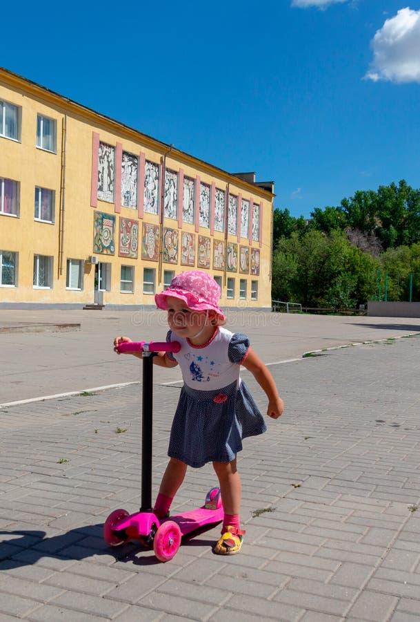 Śliczny dziecko zręcznie jeździć na łyżwach na różowej dwukołowej hulajnoga na s fotografia stock