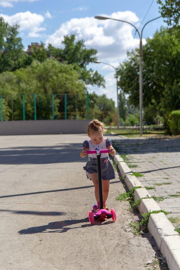 Śliczny dziecko zręcznie jeździć na łyżwach na różowej dwukołowej hulajnoga na s zdjęcie stock