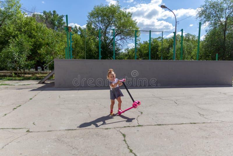 Śliczny dziecko zręcznie jeździć na łyżwach na różowej dwukołowej hulajnoga na s zdjęcie royalty free