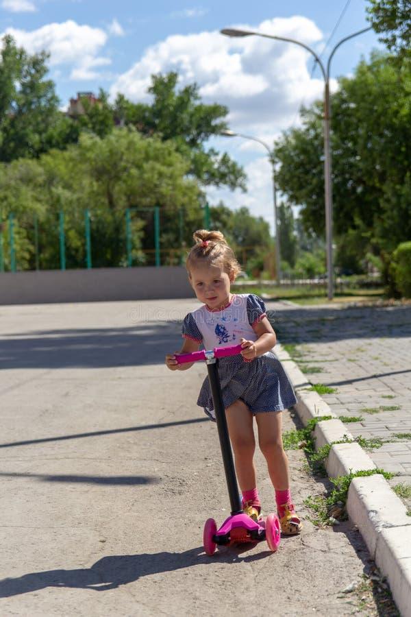 Śliczny dziecko zręcznie jeździć na łyżwach na różowej dwukołowej hulajnoga na s zdjęcia royalty free