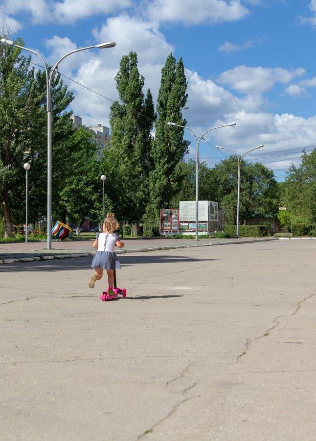 Śliczny dziecko zręcznie jeździć na łyżwach na różowej dwukołowej hulajnoga na s obraz stock