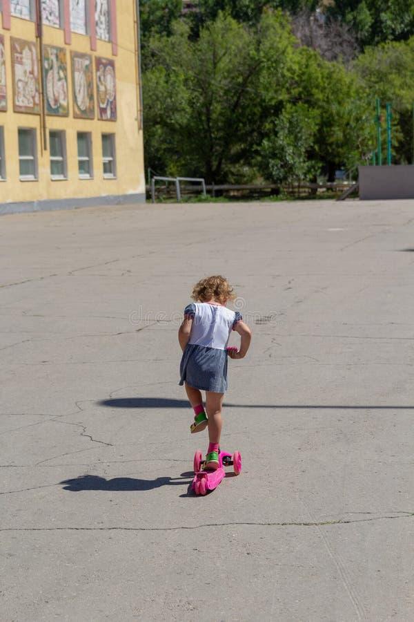 Śliczny dziecko zręcznie jeździć na łyżwach na różowej dwukołowej hulajnoga na s obrazy royalty free