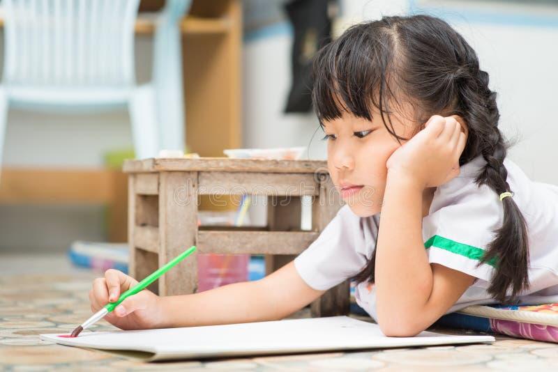 Śliczny dziewczyna uczeń cieszy się malować kolor obraz royalty free