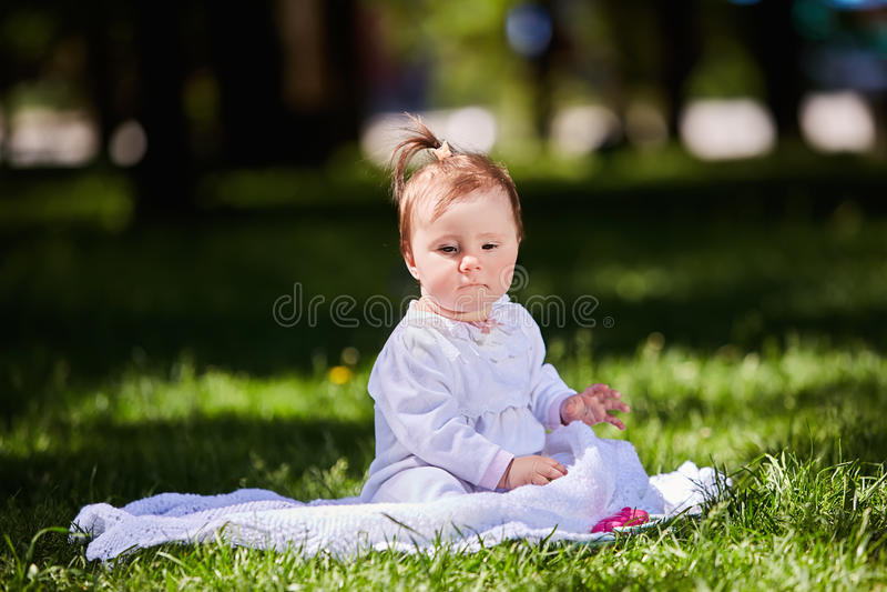 Śliczny dziewczynki obsiadanie na zielonej trawie w miasto parku przy ciepłym letnim dniem zdjęcie stock