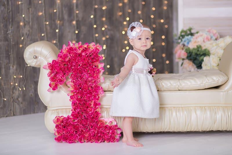 Śliczny dziewczynki 1-2 roczniaka obsiadanie na podłoga z menchiami szybko się zwiększać w pokoju nad bielem odosobniony amerykan zdjęcie stock