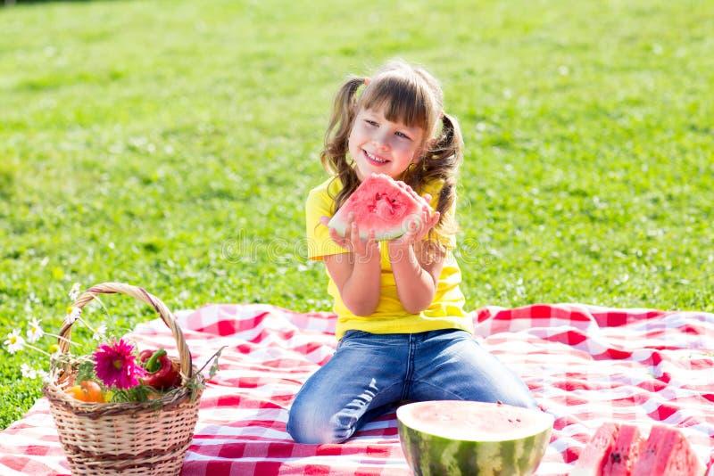 Śliczny dziewczyny łasowania arbuz na trawie wewnątrz fotografia royalty free