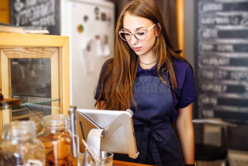 Śliczny dziewczyny barista liczy rachunek w kawowym domu na pastylce obraz royalty free