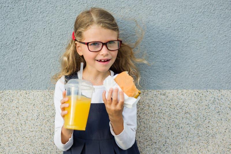 Śliczny dziewczyny 7 lat je kanapkę i pije sok pomarańczowego zdjęcia royalty free