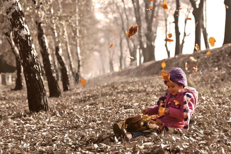 Śliczny dziewczyny obsiadanie na spadać jesień liściach podczas gdy liście spada i bawić się z lalami obraz royalty free